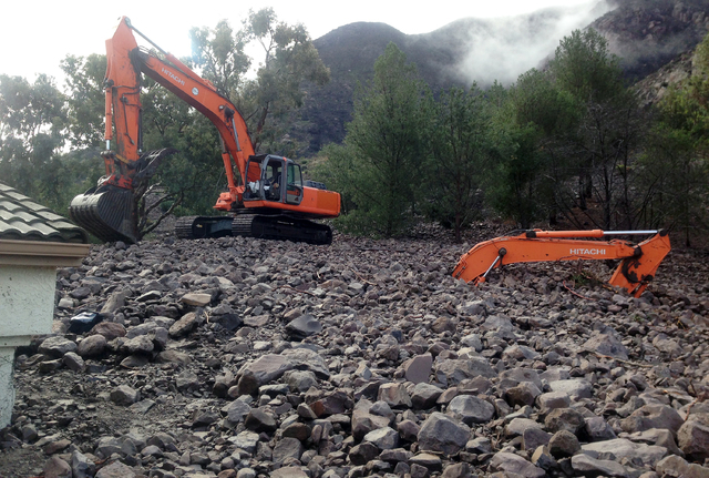CORRECTS WHO HIRE CREW AND ALSO BYLINE TO RAQUEL MARIA DILLON- Earth moving equipment is buried by debris in Camarillo Springs, Calif., about 50 miles northwest of Los Angeles on Friday, Dec. 12,  ...