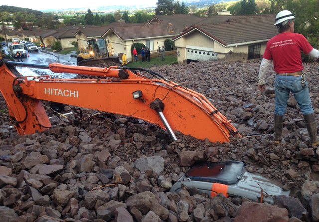 Earth moving equipment is buried by a debris flow in Camarillo Springs, Calif. about 50 miles northwest of Los Angeles on Friday, Dec. 12, 2014.   A soaking storm swept into Southern California, c ...
