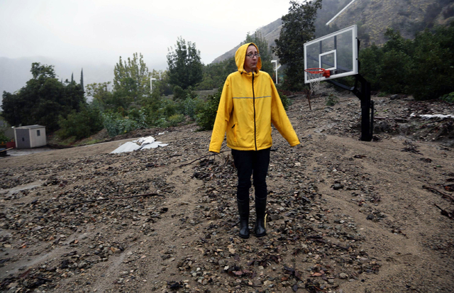 Homeowner Amanda Heinlein stands on a mud landslide covering a basketball court near her house in Azusa, Calif., Friday, Dec. 12, 2014.   A soaking storm swept into  California, causing several mu ...