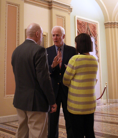 Senate Minority Whip John Cornyn of Texas, center, talks to reporters on Capitol Hill in Washington, Saturday, Dec. 13, 2014, as the Senate continues work near the end of 113th Congress. Their pow ...