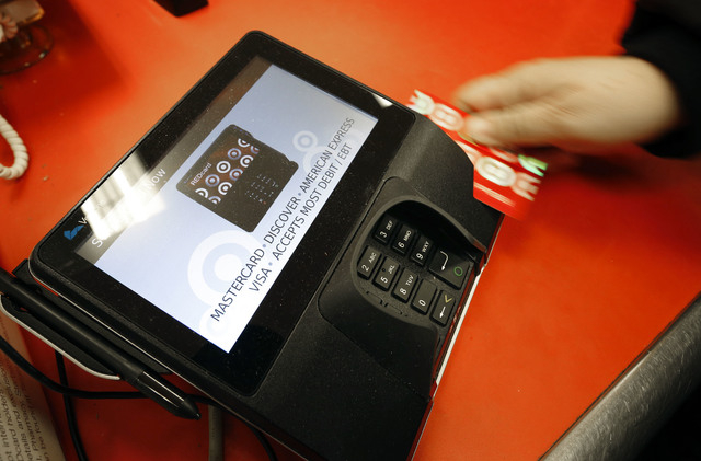 A shopper pays for her purchases at a Target store in South Portland, Maine, Nov. 28, 2014. Criminals stole personal information from tens of millions of Americans in data breaches last year. Of t ...