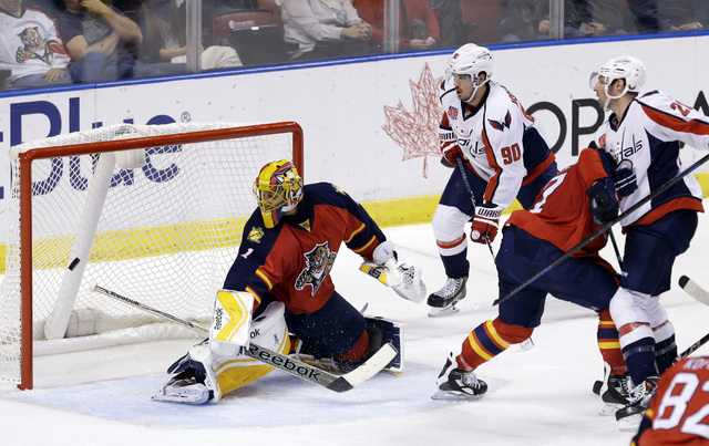 Florida Panthers goalie Roberto Luongo (1) is unable to stop a shot by Washington Capitals right wing Troy Brouwer (20) during the second period of an NHL hockey game, in Sunrise, Fla., Tuesday, D ...