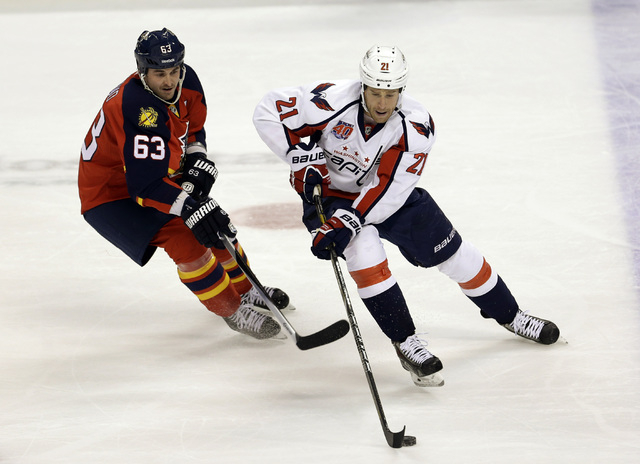 Washington Capitals center Brooks Laich (21) drives as Florida Panthers center Dave Bolland (63) defends during the first period of an NHL hockey game in Sunrise, Fla., Tuesday, Dec. 16, 2014. (AP ...
