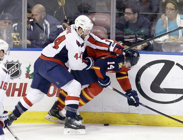 Washington Capitals defenseman Brooks Orpik (44) checks Florida Panthers left wing Tomas Fleischmann (14) during the first quarter of an NHL hockey game, in Sunrise, Fla., Tuesday, Dec. 16, 2014.  ...