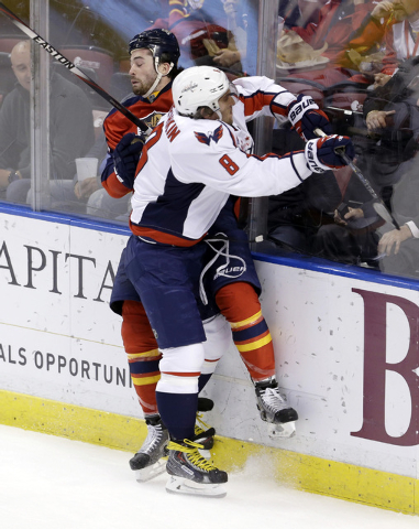 Florida Panthers defenseman Erik Gudbranson, back, is checked by Washington Capitals left wing Alex Ovechkin (8) during the first period of an NHL hockey game, in Sunrise, Fla., Tuesday, Dec. 16,  ...