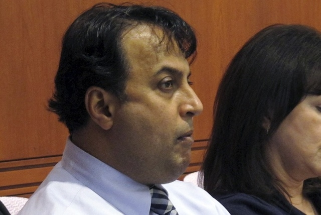 Dentist Rashmi Patel, center, sits with supporters at a hearing of the Connecticut State Dental Commission in Hartford, Conn., Wednesday, Dec. 17, 2014. (AP Photo/Dave Collins)