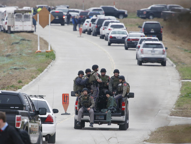 Texas Department of Public Safety officers ride in a pickup to a command post while other officers look for a gunman who shot a weather forecaster during an altercation outside the KCEN-TV studio  ...