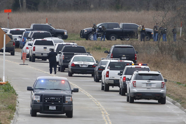 Law enforcement officers set up near a command post while looking  for a gunman who shot a weather forecaster during an altercation outside the KCEN-TV studio along Interstate 35 between Waco and  ...
