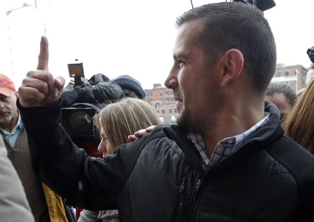 Boston Marathon bombing victim Marc Fucarile signals to protestors as he arrives at federal court in Boston Thursday, Dec. 18, 2014, where bombing suspect Dzhokhar Tsarnaev is scheduled for a fina ...