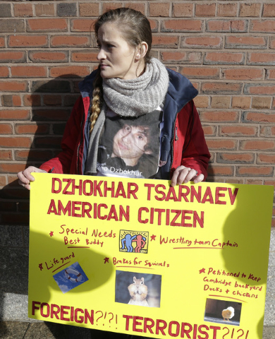 Kimberly Ciaramella holds a sign outside federal court in Boston Thursday, Dec. 18, 2014, while Boston Marathon bombing suspect Dzhokhar Tsarnaev was in a final hearing before his trial begins in  ...