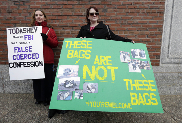Protestors hold signs outside federal court in Boston Thursday, Dec. 18, 2014, where Boston Marathon bombing suspect Dzhokhar Tsarnaev is scheduled for a final hearing before his trial begins in J ...