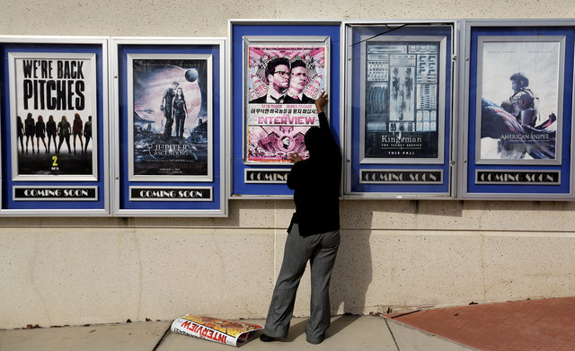 "A poster for the movie ""The Interview"" is taken down by a worker after being pulled from a display case at a Carmike Cinemas movie theater, Wednesday, Dec. 17, 2014, in Atlanta. Georgia- ..."