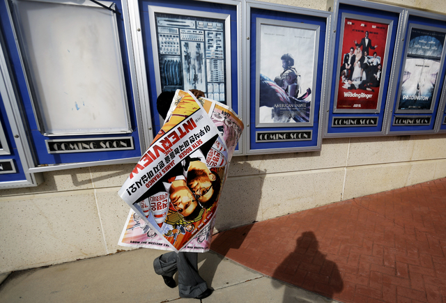 "In this Dec. 17, 2014 file photo, a poster for the movie ""The Interview"" is carried away by a worker after being pulled from a display case at a Carmike Cinemas movie theater in Atlanta. Suspicion ..."