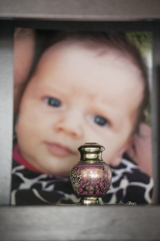 In this Nov. 13, 2014, photo, a small urn containing the ashes of Mattisyn Blaz is displayed on a bookshelf in front of a photo of the infant girl in the home of Jennifer Blaz, 34, in Butte, Mont. ...