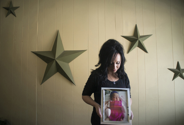 In this Nov. 13, 2014, photo, Jennifer Blaz, 34, poses for a photo in her home in Butte, Mont., holding a photograph of her daughter, Mattisyn Blaz.Matthew Blaz, 33, was sentenced to life in priso ...