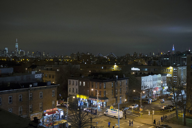 The skyline of Manhattan is seen in the background as investigators work at the scene where two NYPD officers were shot, Saturday, Dec. 20, 2014 in the Bedford-Stuyvesant neighborhood of the Brook ...