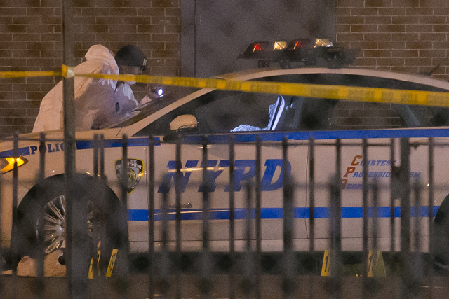 Investigators work at the scene where two NYPD officers were shot, Saturday, Dec. 20, 2014 in the Bedford-Stuyvesant neighborhood of the Brooklyn borough of New York. Police said an armed man walk ...