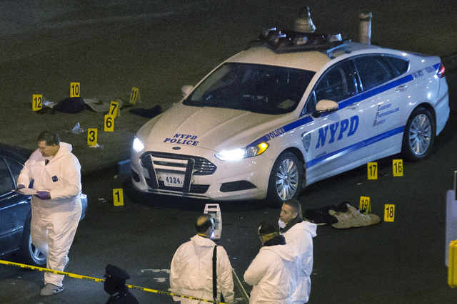 Bulletproof vests lie on each side of an NYPD patrol car as investigators work at the scene where two NYPD officers were shot in the Bedford-Stuyvesant neighborhood of the Brooklyn borough of New  ...