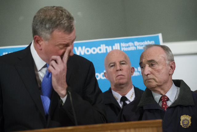 NYPD Commissioner Bill Bratton, right, stands beside Mayor Bill de Blasio as he wipes his eye during a news conference at Woodhull Medical Center, Saturday, Dec. 20, 2014, in New York.  An armed m ...