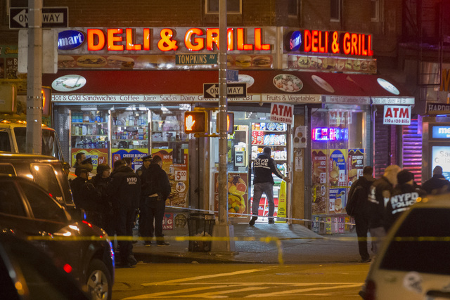 Investigators work in the area where two NYPD officers were shot in the Bedford-Stuyvesant neighborhood of the Brooklyn borough of New York on Saturday, Dec. 20, 2014. Police said an armed man wal ...