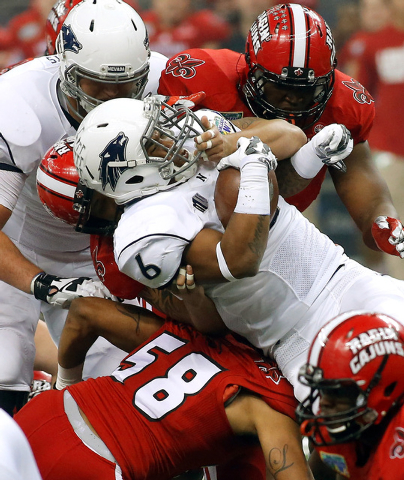 Nevada running back Don Jackson (6) is tackled by Louisiana-Lafayette safety Stephen Morella (58) during the first half of the New Orleans Bowl NCAA college football game in New Orleans, Saturday, ...
