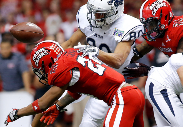 Louisiana-Lafayette cornerback Sean Thomas (24) forces a fumble on Nevada wide receiver Wyatt Demps (80) during the first half of the New Orleans Bowl NCAA college football game in New Orleans, Sa ...