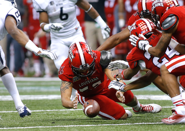 Louisiana-Lafayette defensive end Dominique Tovell, center, recovers a fumble during the first half of the New Orleans Bowl NCAA college football game against Nevada in New Orleans, Saturday, Dec. ...