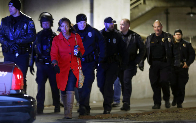 Law enforcement officers, some equipped with riot gear, and others leave the east parking entrance at Mall of America Saturday, Dec. 20, 2014, in Bloomington, Minn. The group Black Lives Matter Mi ...