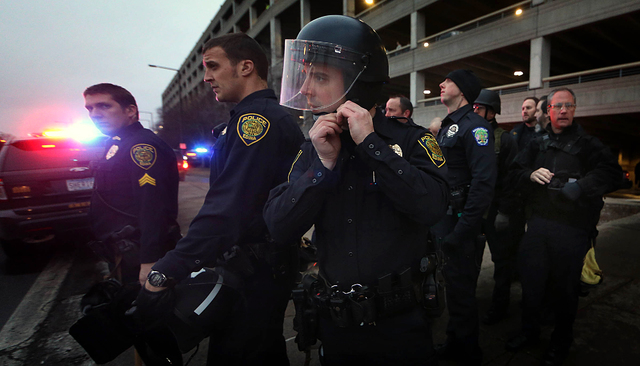 Law enforcement officers, some equipped with riot gear, waited to cross 24th Ave. S. as they left the MOA through the east parking entrance at Mall of America Saturday, Dec. 20, 2014, in Bloomingt ...