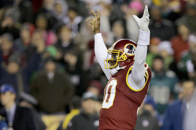 Washington Redskins quarterback Robert Griffin III celebrates running back Alfred Morris's touchdown during the first half of an NFL football game against the Philadelphia Eagles in Landover, Md., ...