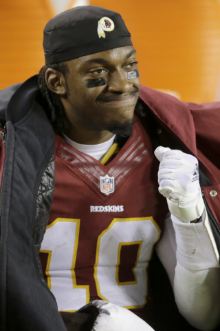 Washington Redskins quarterback Robert Griffin III (10) reacts on the bench during the second half of an NFL football game against the Philadelphia Eagles in Landover, Md., Saturday, Dec. 20, 2014 ...