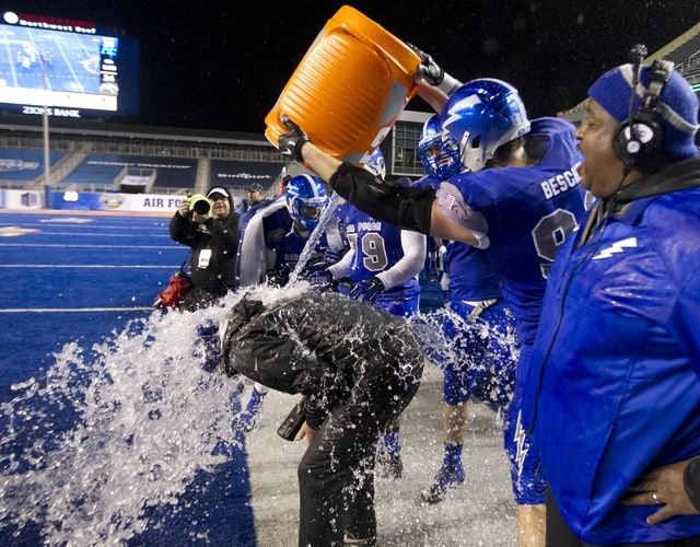 Air Force coach Troy Calhoun gets doused with water by defensive linesman Dillon Beschel (98) at the end of the Famous Idaho Potato Bowl NCAA football game Saturday Dec. 20, 2014,  at Albertsons S ...