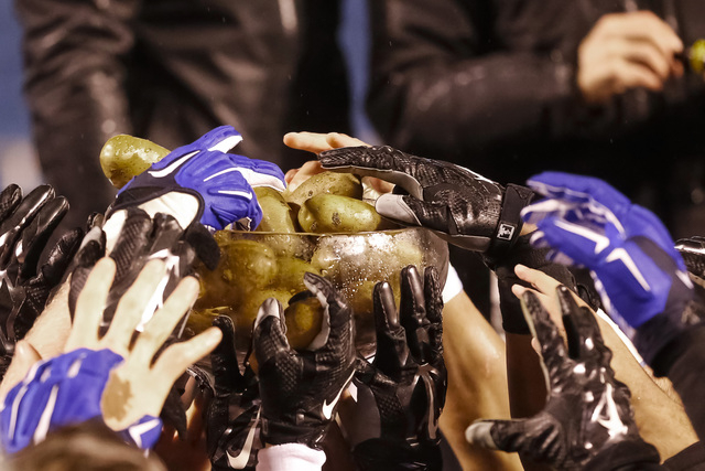 Air Force players grab potatoes out of the trophy after the Famous Idaho Potato Bowl NCAA college football game against Western Michigan in Boise, Idaho, on Saturday, Dec. 20, 2014. Air Force won  ...