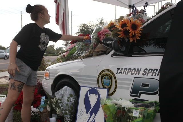 Cynthia Martinez, 23 of Tarpon Springs, leaves flowers at a memorial for a slain Tarpon Springs police officer in Tarpon Springs, Fla. on Sunday, Dec. 21, 2014. The Tarpon Springs Police Departmen ...