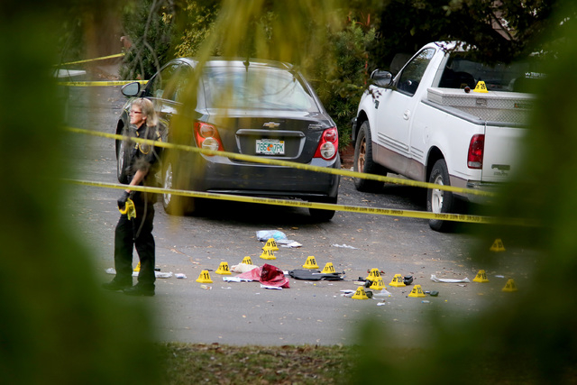 A forensic science investigator with the Pinellas County Sheriff's Office investigates the scene where 45-year-old Tarpon Springs police officer Charles Kondek was shot and killed, Sunday, Dec. 21 ...