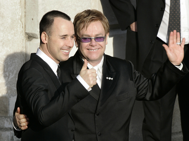 A Wednesday Dec. 21, 2005 photo from files showing pop star Elton John, right, and his longtime partner David Furnish, embracing as they wave to members of the media and the public after they had  ...