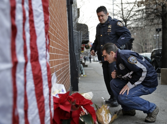 Police officers leave candles at an impromptu memorial near the site where two New York City police officers were killed in the Brooklyn borough of New York, Sunday, Dec. 21, 2014. Police say Isma ...