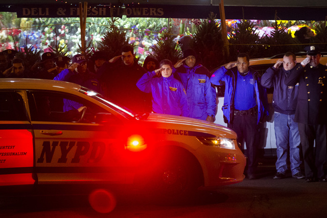 Mourners stand at attention as the bodies of two fallen NYPD police officers are transported from Woodhull Medical Center, Saturday, Dec. 20, 2014, in New York. An armed man walked up to two New Y ...