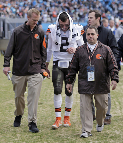 Cleveland Browns' Johnny Manziel (2) is helped off the field after being injured in the first half of an NFL football game against the Carolina Panthers in Charlotte, N.C., Sunday, Dec. 21, 2014.  ...