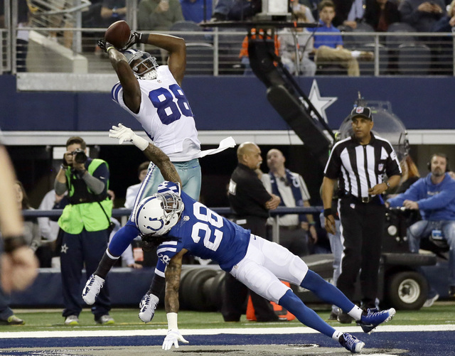 Dallas Cowboys wide receiver Dez Bryant (88) reaches up to grab a touchdown pass over Indianapolis Colts cornerback Greg Toler (28) during the first half of an NFL football game, Sunday, Dec. 21,  ...