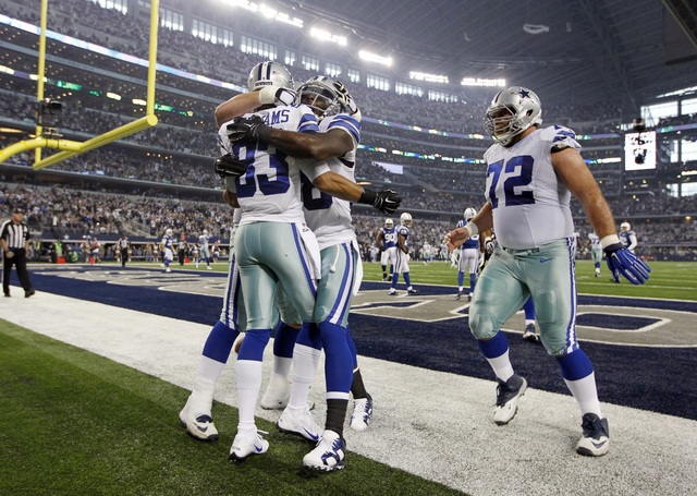 Dallas Cowboys wide receiver Terrance Williams (83) is congratulated by Dez Bryant, center, and Travis Frederick (72) after Williams scored a touchdown on a pass from Romo during the first half of ...