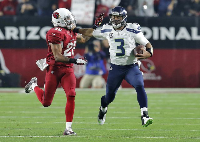 Seattle Seahawks quarterback Russell Wilson (3) tries to avoid a tackle by Arizona Cardinals free safety Rashad Johnson (26) during the first half of an NFL football game, Sunday, Dec. 21, 2014, i ...
