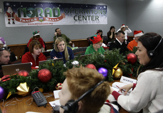 FILE - In this Dec. 24, 2012 file photo, volunteers take phone calls from children asking where Santa is and when he will deliver presents to their house, during the annual NORAD Tracks Santa Oper ...