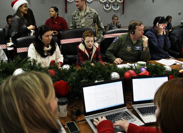 FILE - In this Dec. 24, 2012 file photo, U.S. Air Force Brig. Gen. Richard Scobie, right, his son Andrew, center, and wife, Janis, all take phone calls from children asking where Santa is and when ...