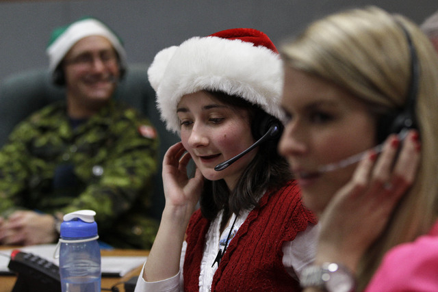 In this Dec. 24, 2012, file photo, volunteer Katherine Beaupre takes phone calls from children asking where Santa is and when he will deliver presents to their house, during the annual NORAD Track ...