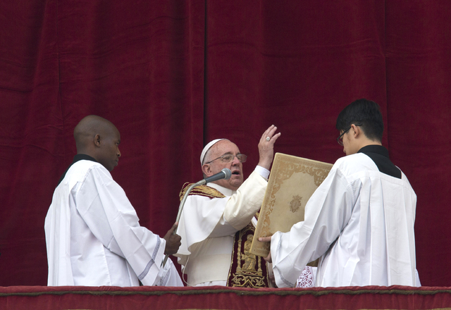 """Pope Francis delivers his """"Urbi et Orbi"""" (to the city and to the world) blessing from the central balcony of St. Peter's Basilica at the Vatican, Thursday, Dec. 25, 2014. (AP Photo/Alessandra Tara ..."""