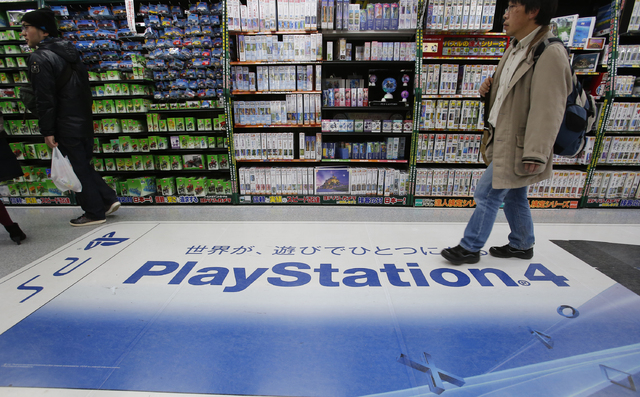 In this Thursday, Dec. 25, 2014 photo, a shopper walks on the logo of Sony's PlayStation 4 at an electronics store in Tokyo. Sony's online PlayStation store and Microsoft's Xbox site suffered disr ...