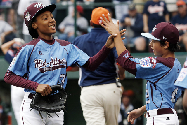 In this Aug. 15, 2014, file photo, Pennsylvania pitcher Mo'ne Davis, left, celebrates with teammate Jack Rice (2) after getting the final out of a 4-0 shutout against Tennessee during a baseball g ...