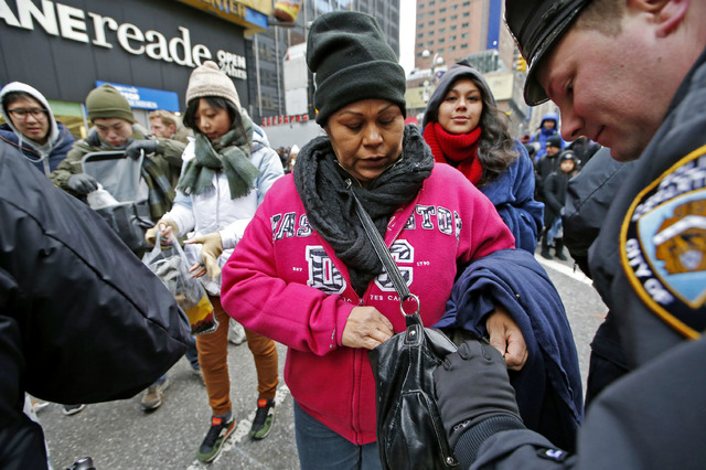 A police officer checks a woman's purse as his colleagues check other spectators' bags at one entrance to Times Square on New Years Eve in New York, Wednesday, Dec. 31, 2014.  Security was said to ...