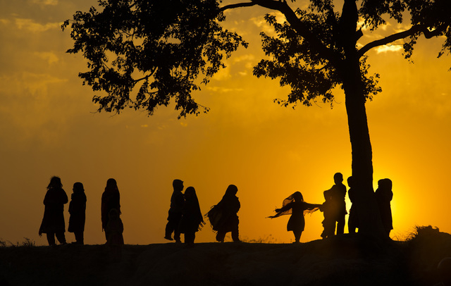 Children displaced from Pakistani tribal areas due to fighting between security forces and militants play under a tree during the last sunset of the year on the outskirts of Islamabad, Pakistan, W ...